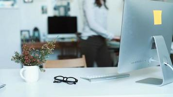 donna che fa alcune note ai progetti mentre si appoggia al tavolo in ufficio