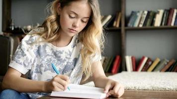 jolie adolescente écrit une lettre dans un cahier