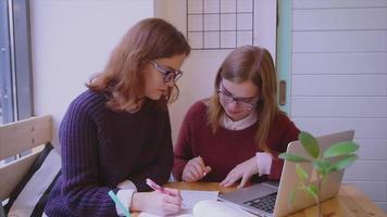 Studentinnen studieren im Café zwei Freundinnen, die zusammen lernen