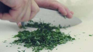 Zeitlupe. das Kochmesser zum Schneiden von Salaten auf einem Schneidebrett