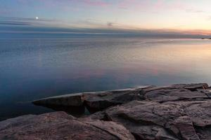 Lago con media luna contra el fondo del resplandor vespertino al sol de medianoche