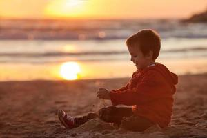 Adorable kid, playing on the beach, sunset time