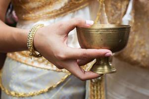 Bride hand holding gold container for pour water ceremony photo