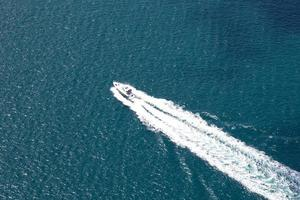 Large wake on blue open ocean left by ferry boat