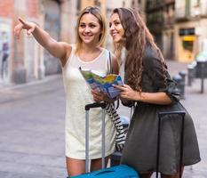 Two women with baggage checking route outdoors photo