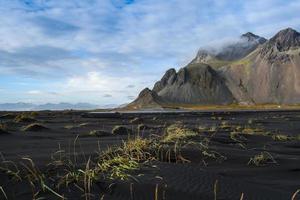 Montañas y arena de lava volcánica en Stokksness, Islandia