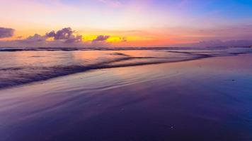 Waves washing up on the sand at sunset photo