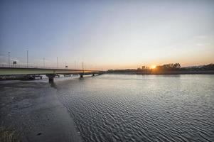 Wide angle image of  bridge over a river at sunset photo
