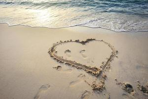 Heart with footprints drawn in the sand photo