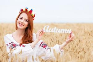 Redhead girl in national ukrainian clothes with wooden word Autu