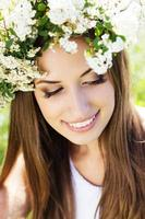 Beautiful girl on the nature in wreath of flowers