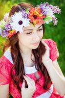 Beautiful young woman with wreath flowers  in the spring garden