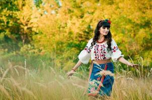 Mujer ucraniana en ropa nacional en el campo de trigo