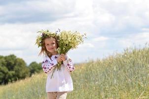 hermosa niña sonriente con ramo de flores silvestres
