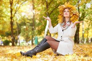 girl sit on leaves in sunny autumn city park photo