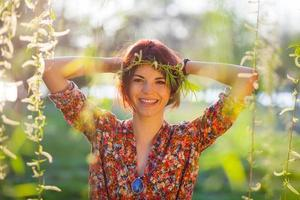 Cute young woman with branches wreath