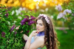 beautiful girl with a flower lilac the sun