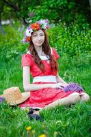 beautiful woman sitting in a wreath on a meadow