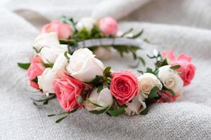tiara of artificial roses on wooden background.