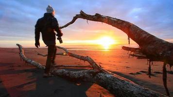 photographer take a photo of sun set on hokitika beach new zealand