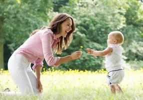 feliz madre enseñando a bebé a caminar en el parque foto
