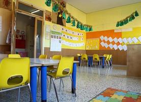 kindergarten classroom with chairs and table with drawings of ch