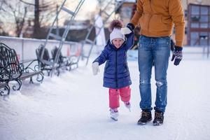 adorável garotinha com o jovem pai na pista de patinação
