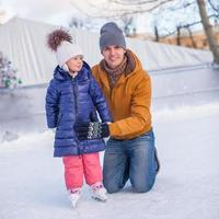Young happy father and adorable little girl on skating rink