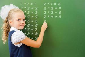 First grade schoolgirl wrote multiplication table on blackboard with chalk photo