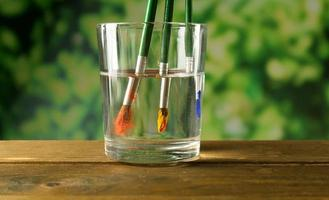 Brush with color paint in glass of water, on table