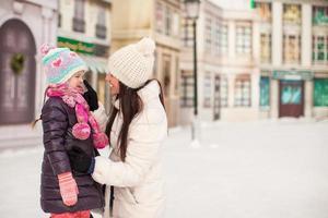 adorável garotinha e sua jovem mãe na pista de patinação