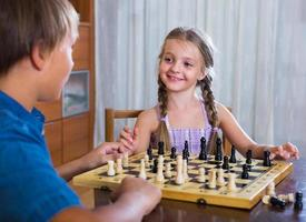 children at chess board indoors photo