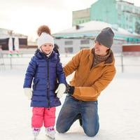 Young father and adorable little girl on skating rink