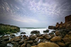 Waves crashing on rocky shore in dawn photo