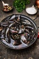 Raw mussels in water on wooden table, preparation for cooking