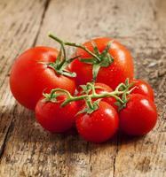 Tomates rojos frescos con gotas de agua sobre la mesa de madera,