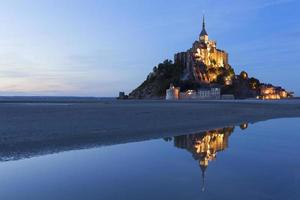 Mount Saint Michael lit up and reflecting in the water