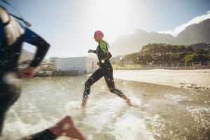 participantes corriendo hacia el agua para el inicio de un triatlón foto