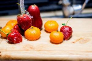 fruta bajo la presión del agua en el fregadero de la cocina foto