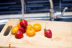 friut bajo la presión del agua en el fregadero de la cocina foto
