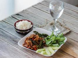 Stir-fried with spicy, thai food, rice in cup and water photo