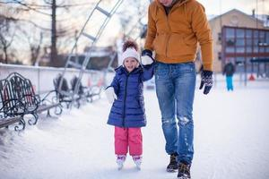 Adorable little girl with young dad on skating rink