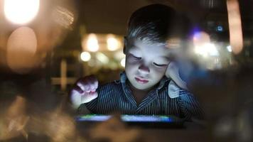 niño jugando en la computadora de la tableta en el café