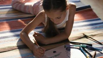 Chica encantadora tumbada en la alfombra dibujando con crayones de colores en el papel