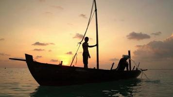 Dos pescadores sacaron agua de un viejo barco de madera al final de un duro día al atardecer en el océano Índico. camara lenta.