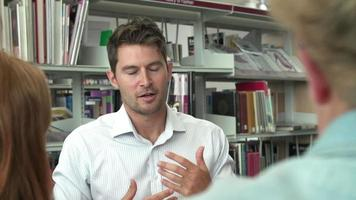 dos estudiantes trabajando juntos en la biblioteca con el maestro