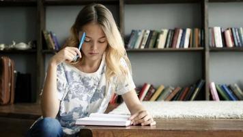 linda garota adolescente escreve uma carta no caderno