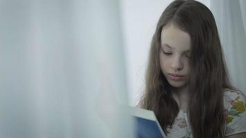 linda garotinha séria lendo um livro pela janela