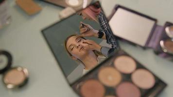 Schreibtisch in einem Schönheitssalon. spiegelte sich im Spiegel ihres kompakten Gesichts des Mädchens. professioneller Stylist video