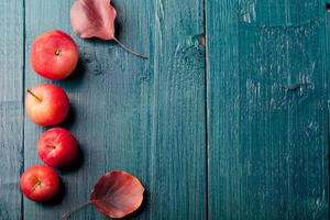 Red apples and leaves Wooden blue, turquoise background photo